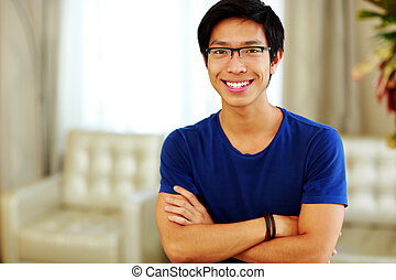 Happy asian man standing with arms folded at home