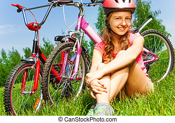 Little girl in red helmet sits on a meadow with two bicycles