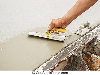 Workers hand using trowel with wet concrete, Construction road w