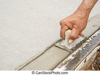 Workers hand using trowel with wet concrete, Construction...