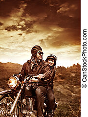 Happy motorcyclists in sunset