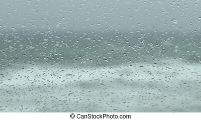 rain on the windshield of car with sea waving background