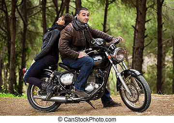 Bikers couple resting in the forest, two models posing on...