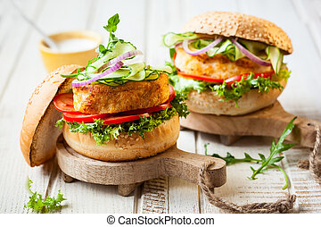 Fish and crab burgers with fresh vegetables on wooden...
