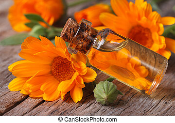 Calendula oil in a glass bottle on an old table horizontal -...