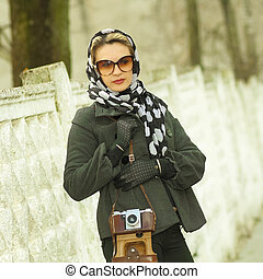 A woman walks down the street with vintage camera