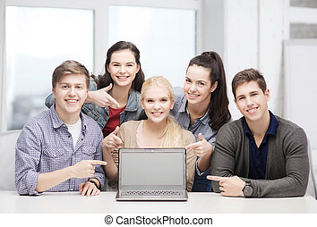 smiling students pointing to blank lapotop screen -...