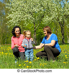 Portrait of happy grandmother, daughter and granddaughter outdoors. Three generations of female blow bubbles