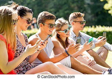 smiling friends with smartphones sitting on grass -...