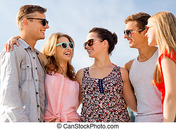 group of smiling friends in city - friendship, leisure,...