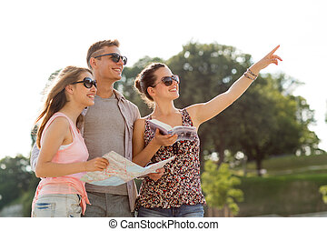 smiling friends with map and city guide outdoors -...