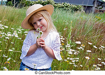 Picking Wildflowers - Little girl in a field of wild...