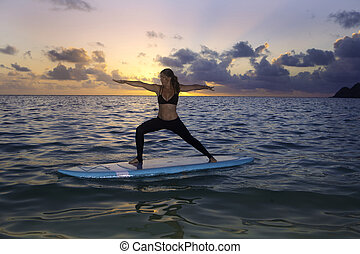 woman doing yoga on a paddle board - woman doing yoga on a...