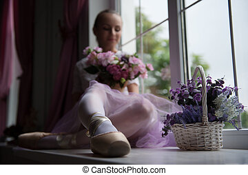Ballet dancer sitting on windowsill holding flowers -...