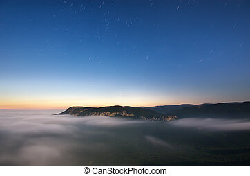 Star trails and mountain. Composition of nature.