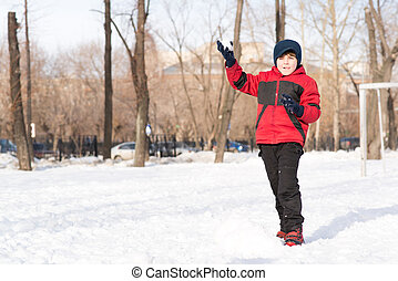 boy in winter park throwing a snowball, extensive time in...