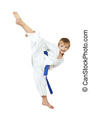 Boy in a kimono performs a kick leg - Boy athlete in a...