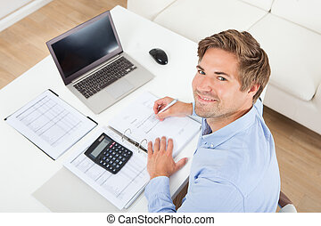 Businessman Calculating Tax At Desk - High angle portrait of...
