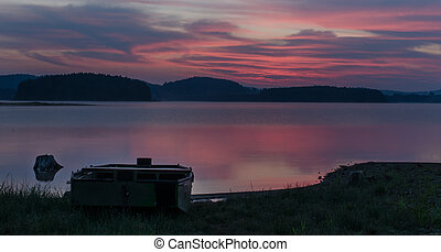 Early morning on the lake Lipno - Boat on shore fishing in...