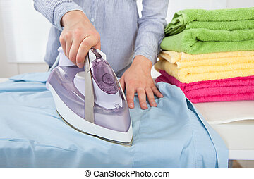 Midsection Of Woman Ironing Shirt - Midsection of woman...