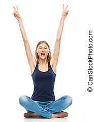 Young happy woman is sitting on the floor and showing...