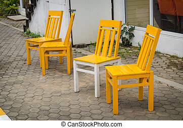 Colourful yellow chairs on the sidewalk,A wooden sun chairs...