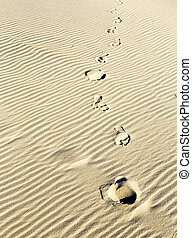background of sand ripples at the beach with prints of feet...