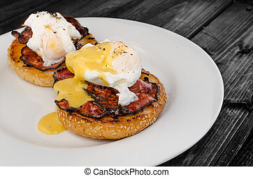 Benedict eggs with crispy bacon and hollandaise sauce on...