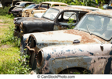 Classic car wreck at a junkyard.