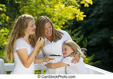 Family of Girls enjoying a moment together while eating fresh fr