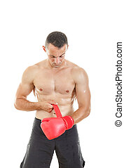 muscular man putting his boxing gloves, preparing for training o