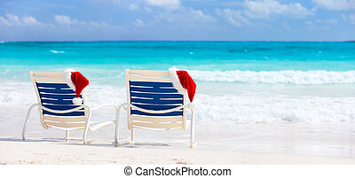 Christmas beach vacation - Two sunloungers with Santa hats...