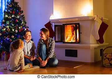 Family at home on Christmas eve - Mother and her two little...