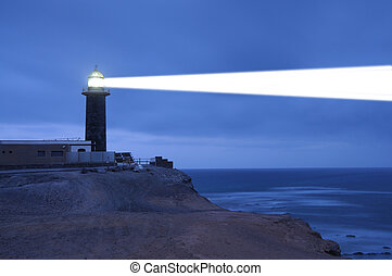Lighthouse searchlight beam through foggy air Punta Jandia,...