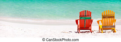 Colorful chairs on Caribbean beach - Two colorful wooden...