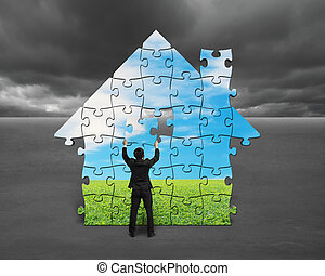 Businessman assembling house shape puzzles with nature image...