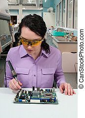 Woman soldering - Beautiful woman repair soldering a printed...