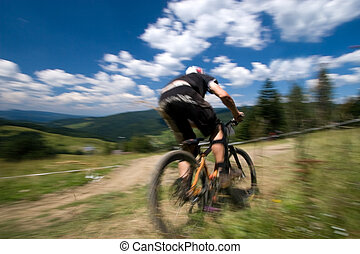 Biker in motion blur - Male mtb biker during downhill event...