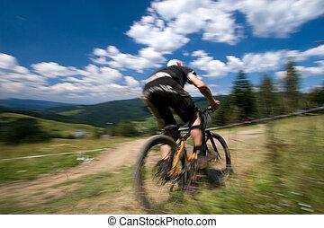 Biker in motion blur - Male mtb biker during downhill event...