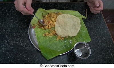 tourist eating vegetarian rice with tomato on banana leaf in...