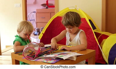 children sketching in home - Two children sketching with...