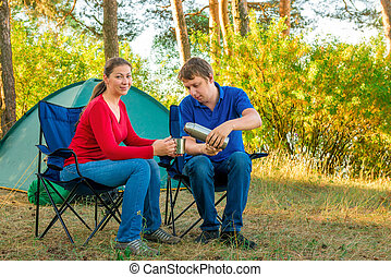 man cares for his wife in the morning at the camp