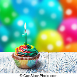 Cupcake with number one on the background of balloons -...