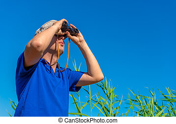 man with binoculars examines bird in the sky