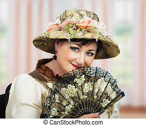 Old actress in hat posing with fan - Face portrait of mature...