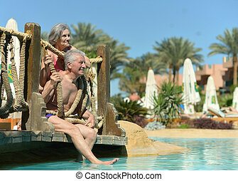 Old couple in pool - Cute old couple sitting by the pool