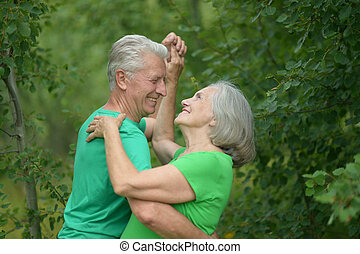 Senior couple dancing in a forest - Senior couple dancing in...