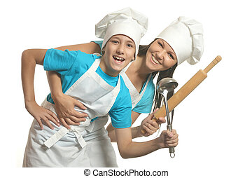 Female chef with assistant holding battledore and soup ladle