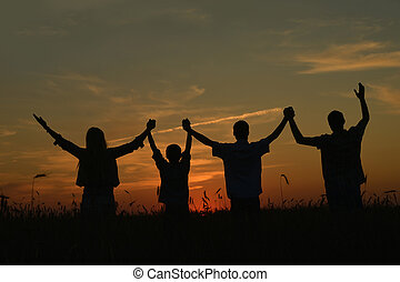Family in field - Family holding hands looking at sunset in...