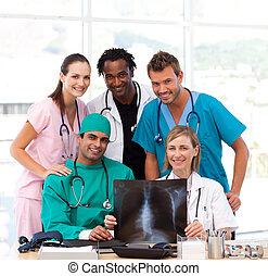 Medical team examining an X-ray and smiling at the camera -...